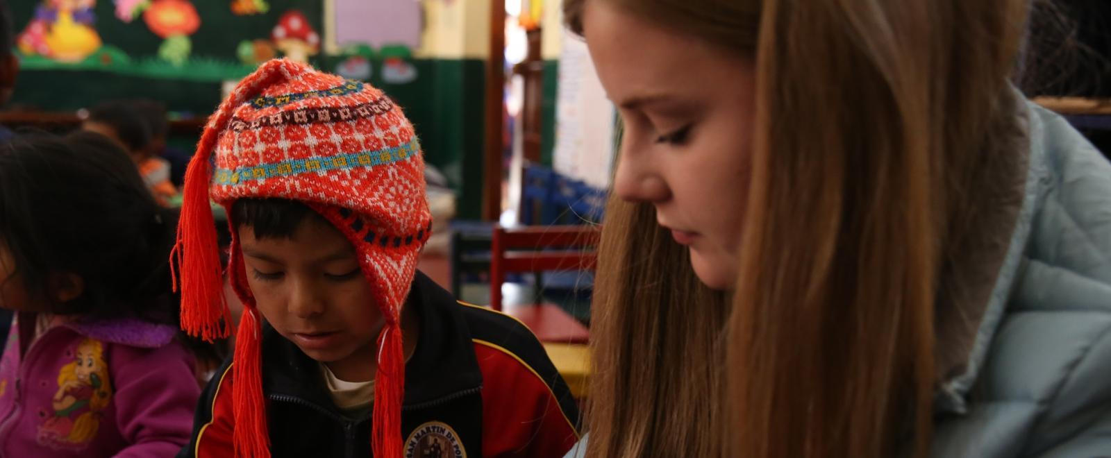 A volunteer working with children in Peru sits with a child in a classroom to help them with an activity.